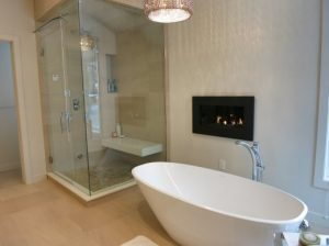 A bathroom renovation with a bathtub and shower done by Refine Renovations.